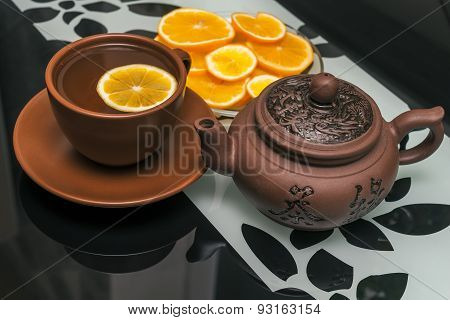ceramic cup of tea and tea pot with lemon