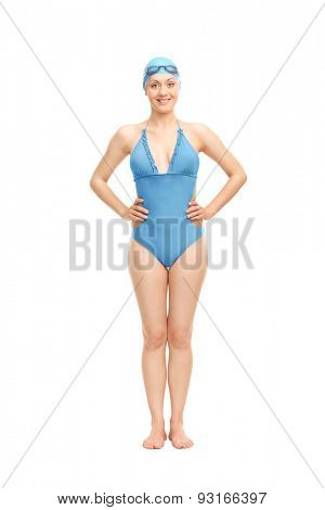 Full length portrait of a female swimmer in a blue swimming costume and a swim cap smiling and looking at the camera isolated on white background