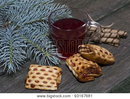 The Glass Of Tea Decorated With Different Cookies And A Branch Of A Fir-tree