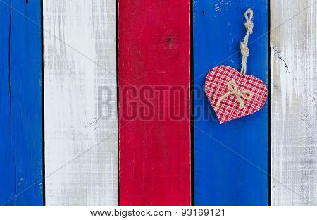 Red heart hanging on red, white and blue painted wood fence