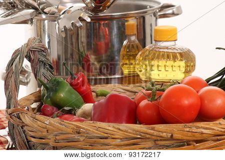 Tomatoes, peppers and other veggies with oil and cook pot in the background.