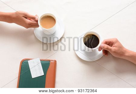 A man and woman reaching for their coffee cups across a cafe table. Overhead closeup with only the peoples hands being shown.