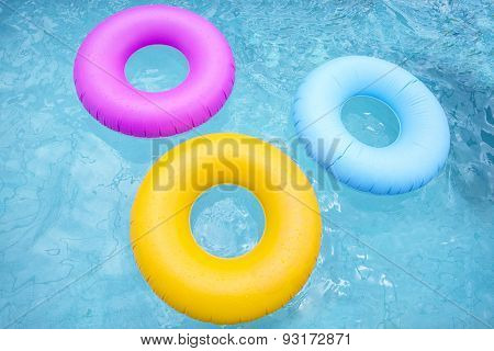 Group of colorful inflatable tubes floating in a swimming pool