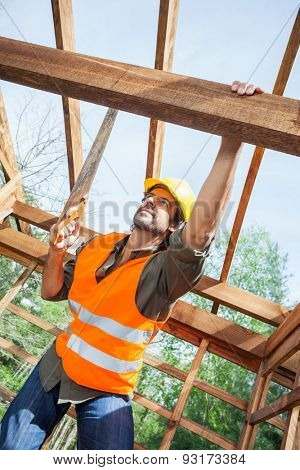 Low angle view of male construction worker cutting wood with handsaw at site