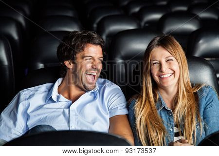 Cheerful mid adult couple laughing while watching film in movie theater