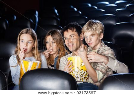 Family of four eating popcorn while watching film in movie theater