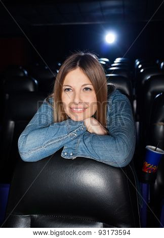 Smiling woman leaning on seat while watching film at cinema theater