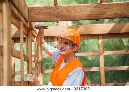 Male construction worker hammering nail on wooden cabin at site