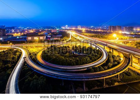 Illuminated skyline and overpass in modern city at night
