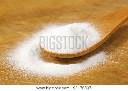 spoon of cooking soda on wooden cutting board