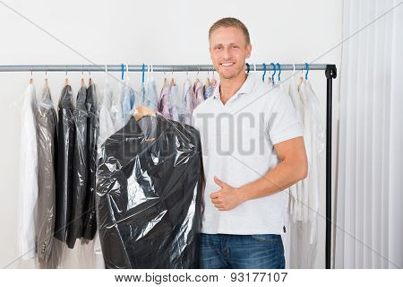 Young Man With Coat In Dry Cleaning Store