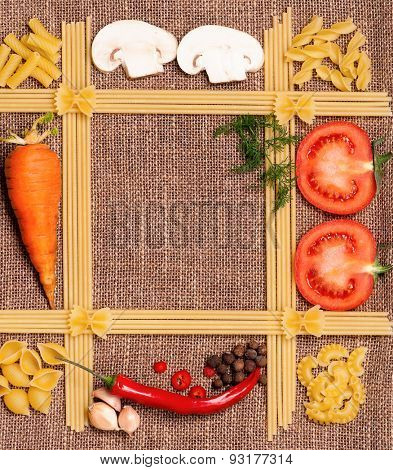 Space for recipes with pasta, vegetables, and spices on burlap
