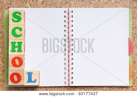 Back to school concept. Blank notebook with spiral bind spine and wooden toy cubes with letters on a wood background.