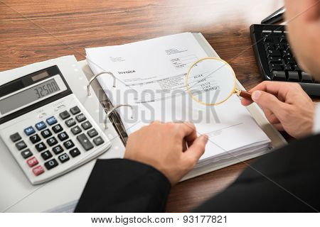 Businessman Looking At Invoice Through Magnifying Glass
