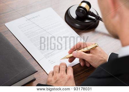 Judge Signing Contract Paper At Desk