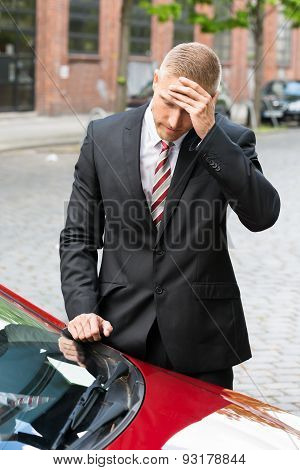 Sad Driver Looking At Parking Ticket On Car