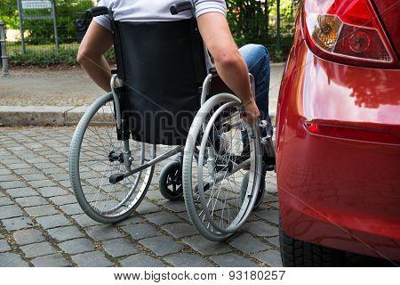 Disabled Man Sitting On A Wheelchair Near His Car