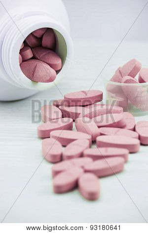 Pink pills an pill bottle on the table.