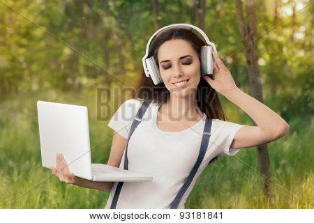 Happy Girl with Headphones and Laptop Listening to Music