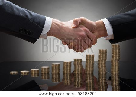 Businessmen Shaking Hands With Coins