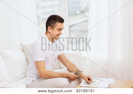 business, savings, finances, income and people concept - man with papers and calculator at home