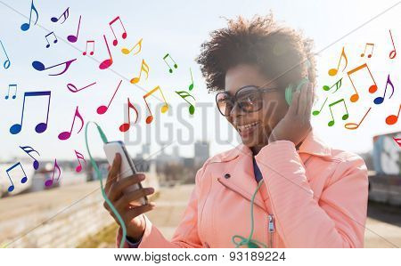 technology, lifestyle and people concept - smiling african american young woman or teenage girl with smartphone and headphones listening to music outdoors over colorful musical notes background