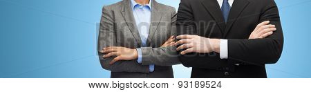 business, people, cooperation and education concept - close up of businesswoman and businessman with crossed arms over blue background