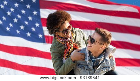 international friendship, freedom and people concept - happy teenage couple in shades having fun over american flag background
