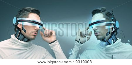 people, technology, future and progress - man in futuristic 3d glasses and microchip implant or sensors over blue background with cyber clone or copy