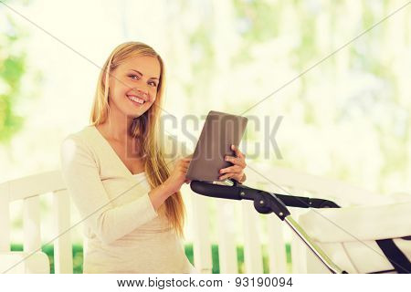 family, parenthood, technology and people concept - happy mother with with tablet pc computer and baby stroller in park