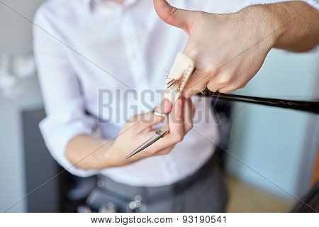 beauty, hairstyle and people concept - male stylist hands with scissors and comb cutting hair tips at salon
