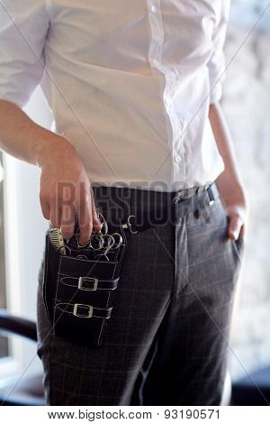 beauty, hairstyle and people concept - close up of male stylist with tool case on belt at salon