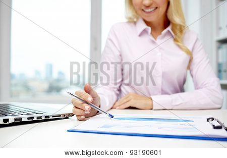 education, business, people and technology concept - close up of smiling businesswoman with laptop computer and papers sitting in office