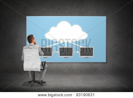 business, people, transferring data and technology concept - businessman in suit sitting in office chair over screen with cloud and server computers on gray wall background from back