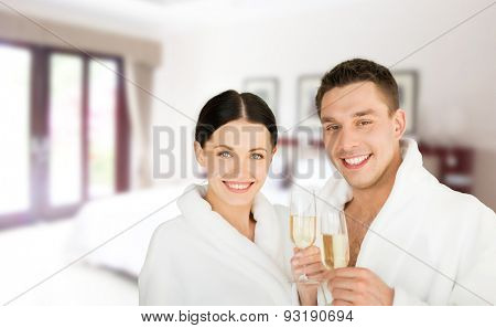 people, travel, tourism, vacation and honeymoon concept - happy couple in bathrobes over spa hotel room background