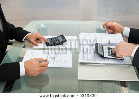Two Businessman Using Calculator In Office