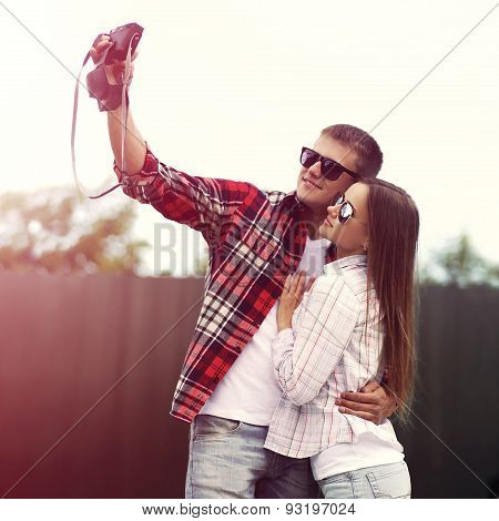 Beautiful Young Couple Making Self-portrait On The Camera And Having Fun Together Outdoors, Soft Vin