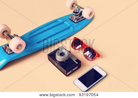 Fashion Look Concept. Blue Skateboard, Red Sunglasses, Vintage Camera And Screen Smartphone. Trendy