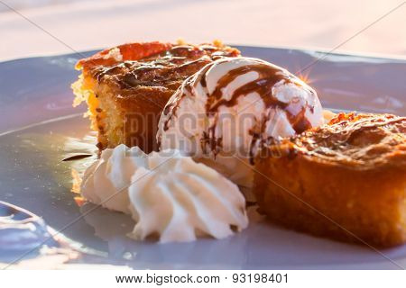 Two Pieces Of Pie With Ice Cream In A White Plate At The  Evening Sun Rays