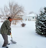 image of snow shovel  - African american male shoveling winter snow at his house outdoors.