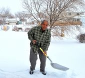 picture of snow shovel  - African american male shoveling winter snow at his house outdoors.