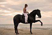 picture of woman legs  - beautiful black stallion on the beach with young woman