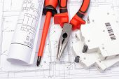 picture of electrical engineering  - Rolled electrical diagrams electric fuse and work tools lying on construction drawing of house drawings for the projects engineer jobs - JPG