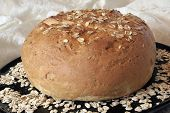 picture of whole-wheat  - horizontal side view of a whole round loaf of oat bread sitting on a round black platter with rolled oats sprinkled on the top of the loaf and the platter against a background of off - JPG