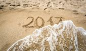 image of off-shore  - Closeup shot of 2017 written on sand being washed off by wave - JPG