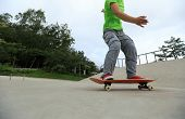image of skateboard  - young skateboarder legs riding skateboard at skatepark - JPG