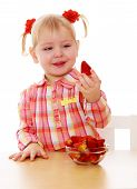 pic of strawberry blonde  - Adorable little girl holding a strawberry sitting at the table - JPG