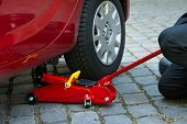 picture of hydraulics  - Car Lifted With Red Hydraulic Floor Jack For Repairing - JPG