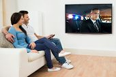 image of watching movie  - Happy Young Couple In Livingroom Sitting On Couch Watching Movie - JPG