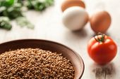 picture of ceramic bowl  - Composition with ceramic bowl dry buckwheat eggs and tomatoes - JPG